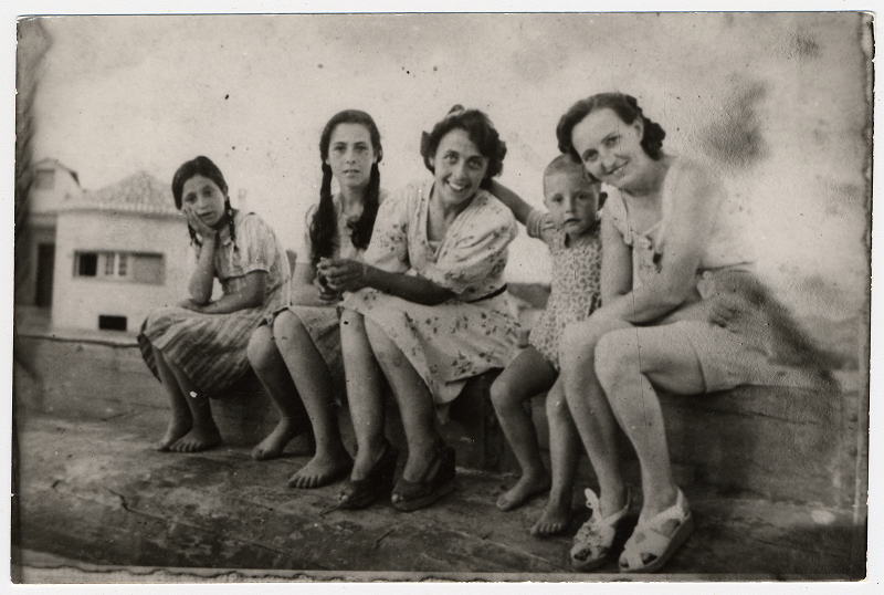 A Jewish mother and child in hiding in Albania sit on a wooden ledge together with their rescuer and her family, Circa 1941-1942. Credit: United States Holocaust Memorial Museum, courtesy of Johanna Neumann