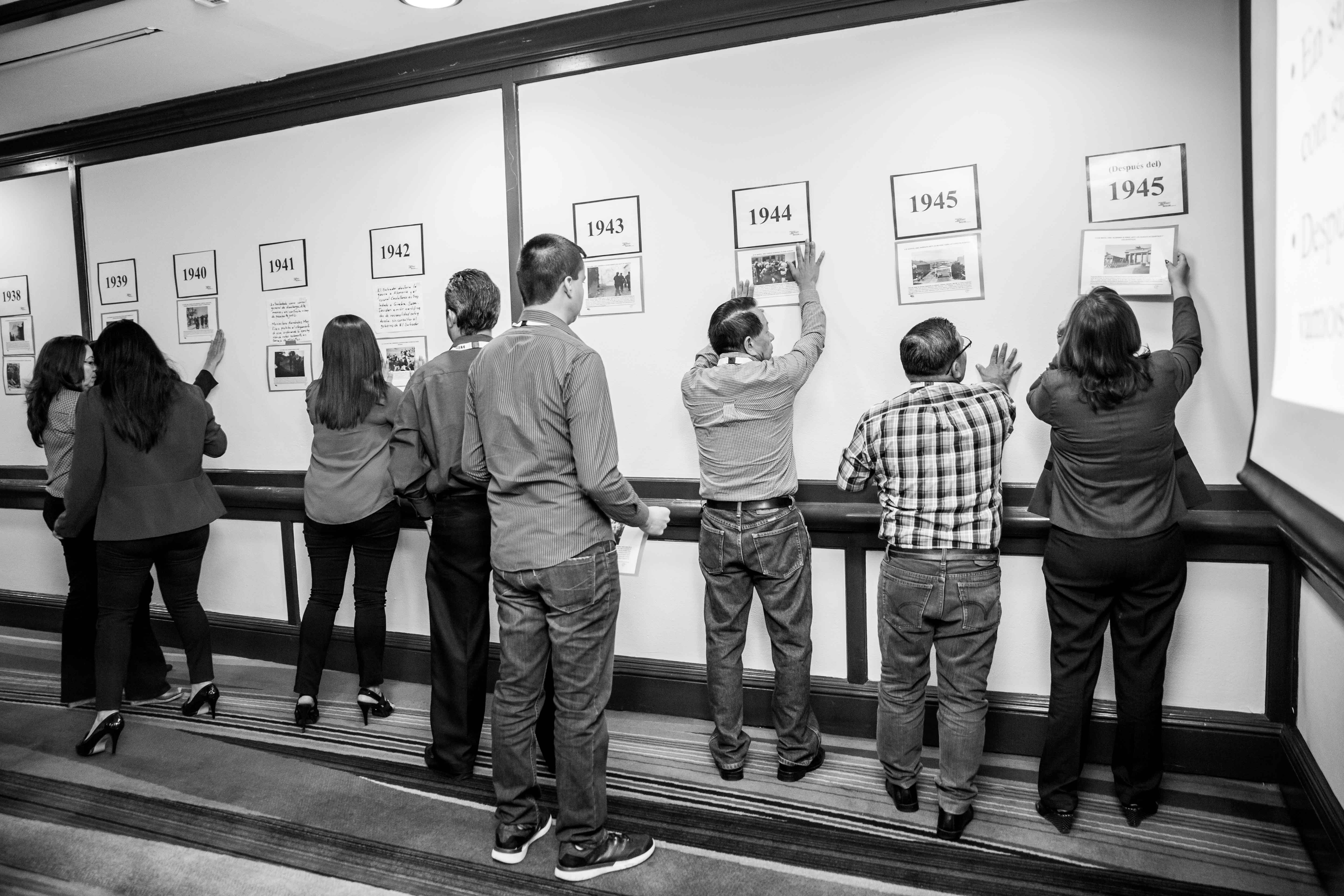 People standing in front of a timeline in a classroom, by Luis Paredes