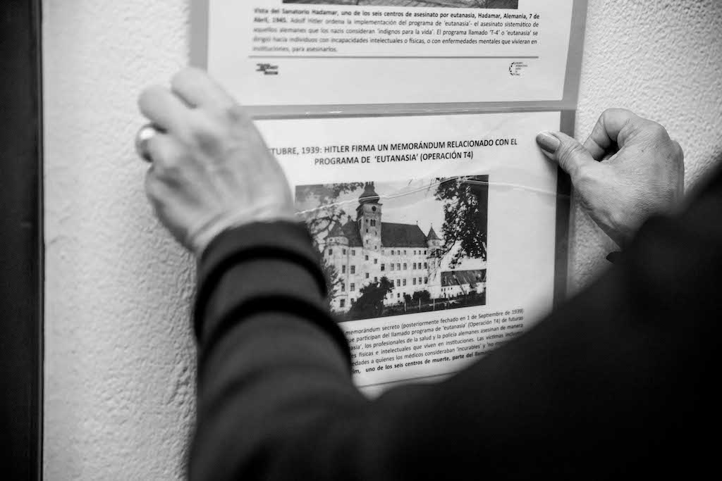 Hands putting up a poster, Holocaust education