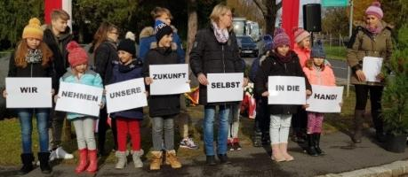 "School children attend commemoration of Genocide of the Roma at former ""gypsy camp"" Lackenbach, Austria, holding signs."