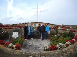 Team members and experts of the IHRA's Safeguarding Sites Project at a memorial for victims on Alderney