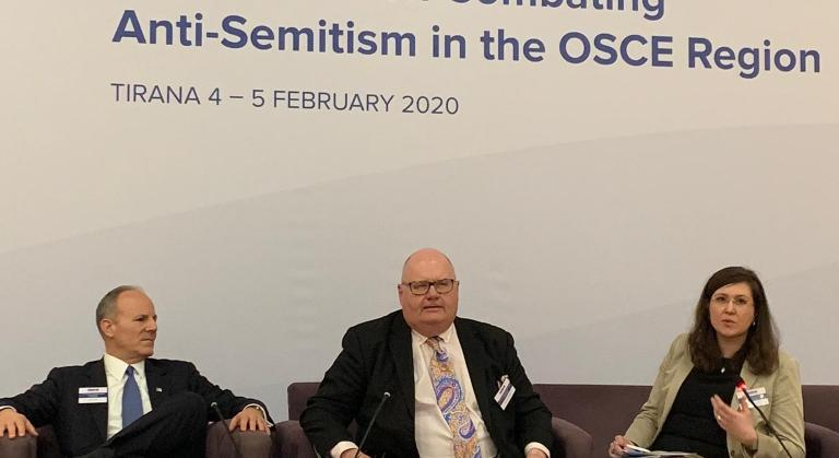 Three people seated on stage for panel discussion during OSCE antisemitism conference.