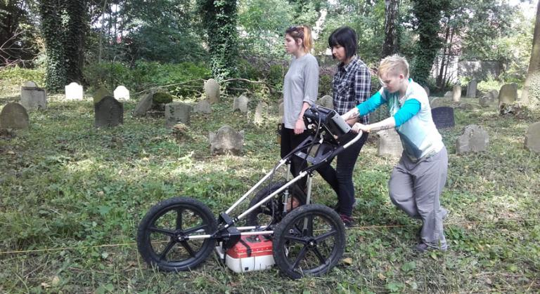 The team uses Ground Penetrating Radar (GPR) during fieldwork at a Jewish cemetery.